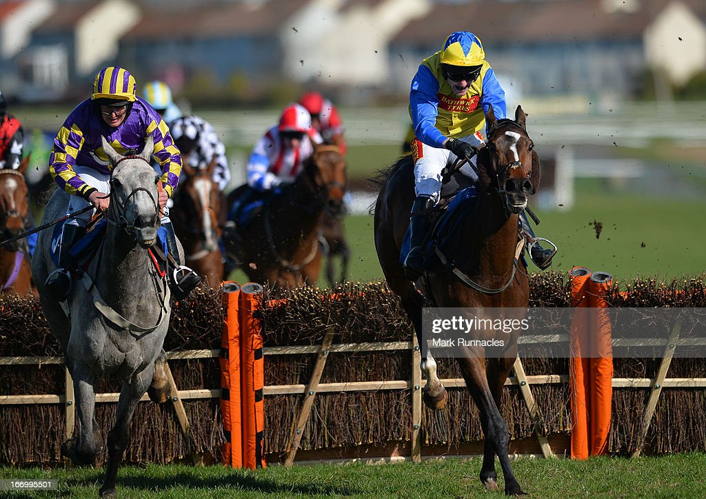 Jockey Tom Scudamore riding Amigo (blue & yellow hat) races with Jockey Michael McAlister on Howzie (Blue & Purple hat) in the Befriend Johnnie Delta Racing On Facebook Handicap Hurdle Race (4:25), at Ayr racecourse on April 19, 2013 in Ayr, Scotland.