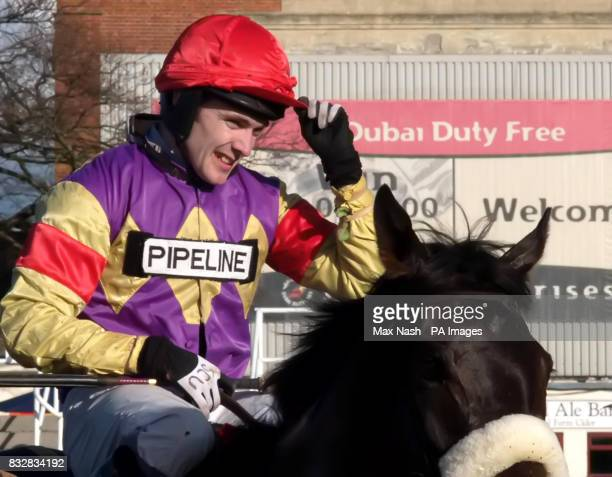 Jockey Tom Scudamore tips his helmet as he brings Madison Du Berlais into the paddock after winning the Vc Casinocom Gold Cup Handicap Chase at...