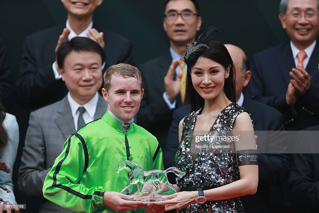 Jockey Tommy Berry receives his trophy from an Audemars Piguet representative after wining the Audemars Piguet Queen Elizabeth II race at Sha Tin racecourse on April 28, 2013 in Hong Kong, Hong Kong.