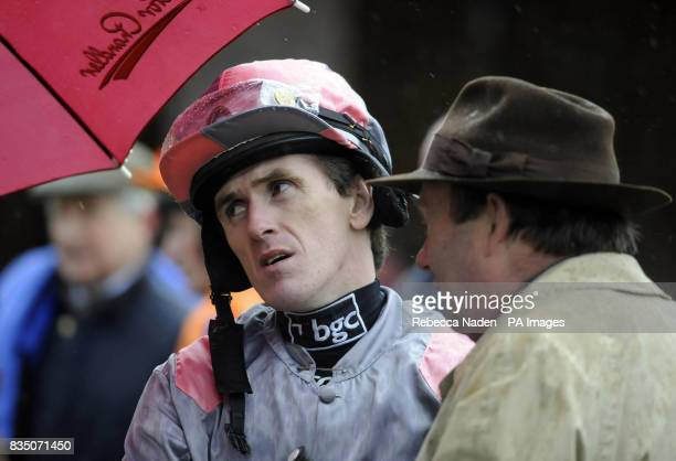 Jockey Tony McCoy talks to trainer Nicky Henderson before finishing seventh on Excape in the Weatherbys Bank Juvenile Novices' Hurdle at Plumpton...