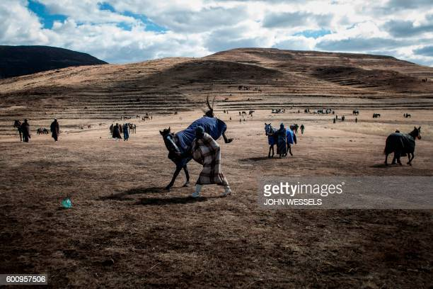 A jockey tries to control his horse as they wait for the races to start on July 16 2016 in Semonkong Horseracing in the mountain kingdom of Lesotho...