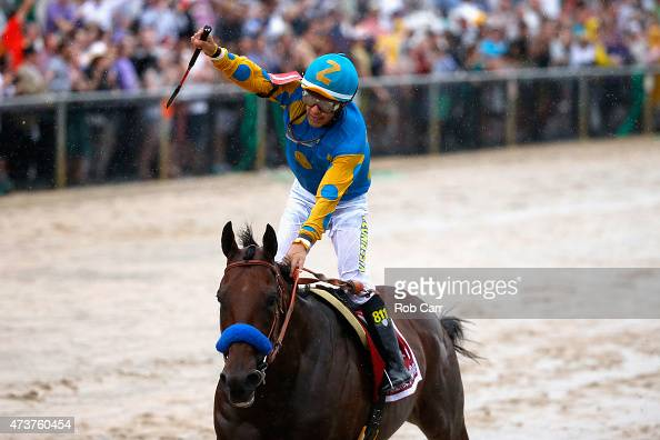 Jockey Victor Espinoza celebrates aboard American Pharoah after crossing the finish line to win the 140th running of the Preakness Stakes at Pimlico...