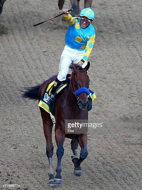 Jockey Victor Espinoza celebrates as he guides American Pharoah after he crossed the finish line as during the 141st running of the Kentucky Derby at...