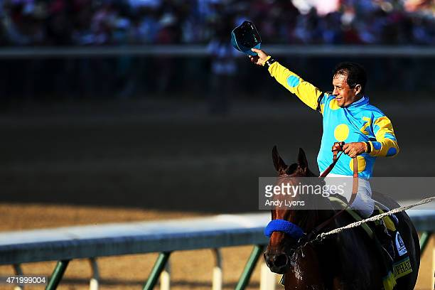 Jockey Victor Espinoza celebrates atop of American Pharoah on his way to winners circle after winning the 141st running of the Kentucky Derby at...