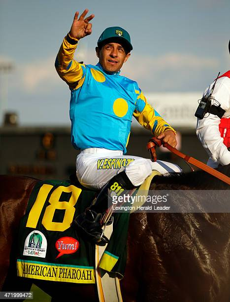 Jockey Victor Espinoza celebrates on the way to the winner's circle after guiding American Pharoah to victory in the 141st running of the Kentucky...