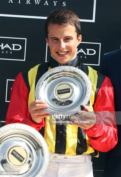 Jockey William Buick celebrates with his trophy after riding Elusive Kate to win The EtihadAirways Falmouth Stakes during Abu Dhabi Gentlemen's Day...