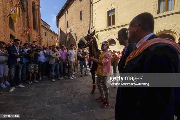 A jockey with the horse attend the blessing of the horses ahead of today's Palio on August 16 2017 in Siena Italy The Palio is the most famous event...