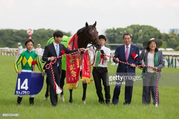 Jockey Yuga Kawada trainer Yasutoshi Ikee and owner Hajime Satomi celebrate after Satono Aladdin winning the Yasuda Kinen at Tokyo Racecourse on June...