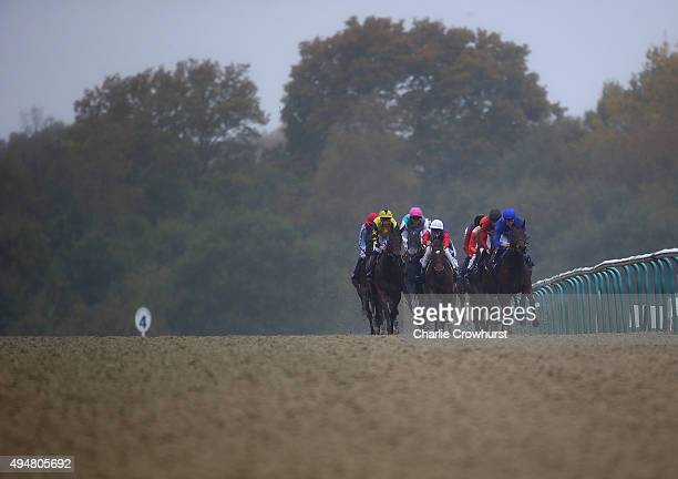 Jockeys and horses run in The 32Red Casino/British Stallion Studs EBF Maiden Fillies' Stakes at Lingfield Park on October 29 2015 in Lingfield England