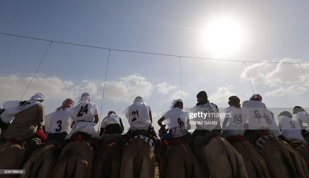 Jockeys compete in a camel race during the Sheikh Sultan Bin Zayed al-Nahyan herithe festival, held at the Shweihan racecourse in Al-Ain, on the outskirts of Abu Dhabi, on February 12, 2016. The festival includes a camel beauty contest, a traditional souq, a camel auction, and competitions for traditional handicrafts. / AFP / KARIM SAHIB