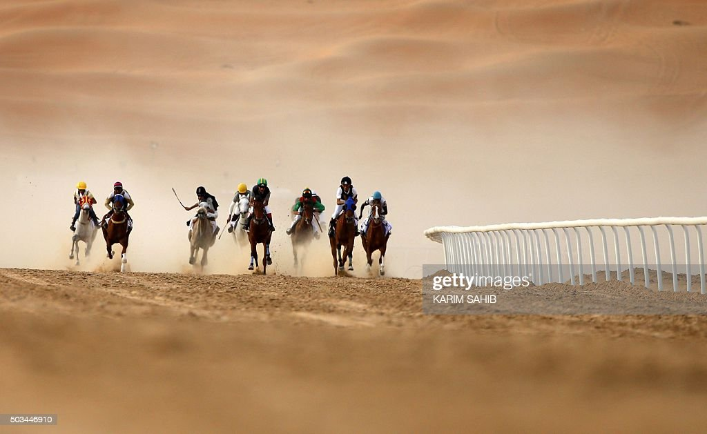 Jockeys compete in a race for purebred Arab horses during the Liwa 2016 Moreeb Dune Festival on January 5, 2016, in the Liwa desert, 250 kilometres west of the Gulf emirate of Abu Dhabi. The festival, which attracts participants from around the Gulf region, includes a variety of races (cars, bikes, falcons, camels and horses) or other activities aimed at promoting the country's folklore. AFP PHOTO / KARIM