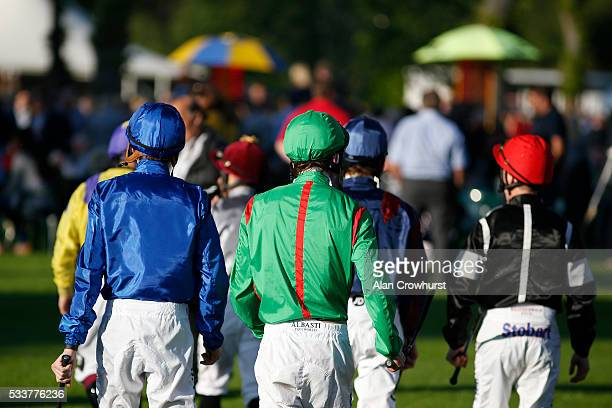 Jockeys make their way across the enclosure to the parade ring at Windsor Racecourse on May 23 2016 in Windsor England