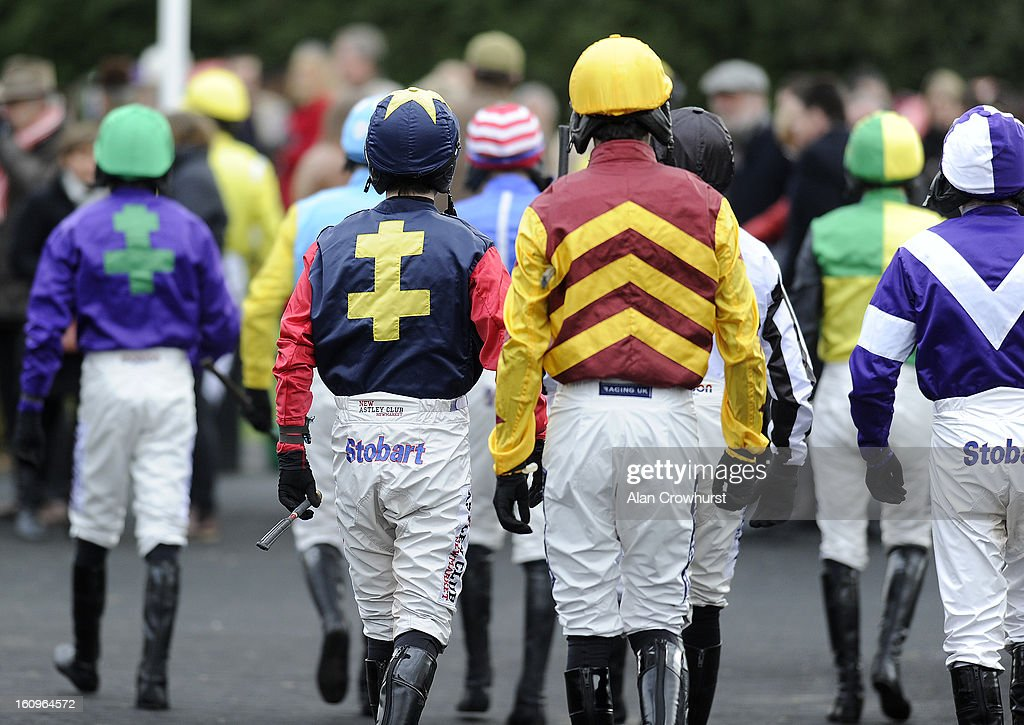 Jockeys make their way into the parade ring to meet the connections at Kempton racecourse on February 08, 2013 in Sunbury, England.
