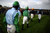 Jockeys make their way to the parade ring at Huntingdon racecourse on October 15 2013 in Huntingdon England