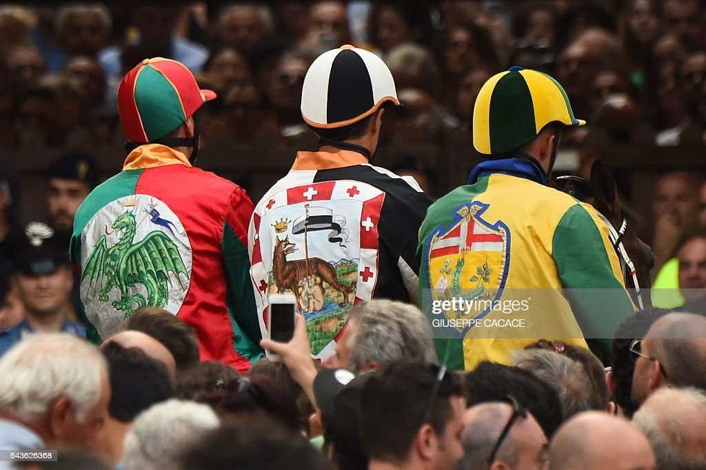 Jockeys of different Contrada wait at the Mossa (the starting line) during a proof-race of the historical Italian horse race of the Palio of Siena on June 29, 2016 in Siena. / AFP / GIUSEPPE