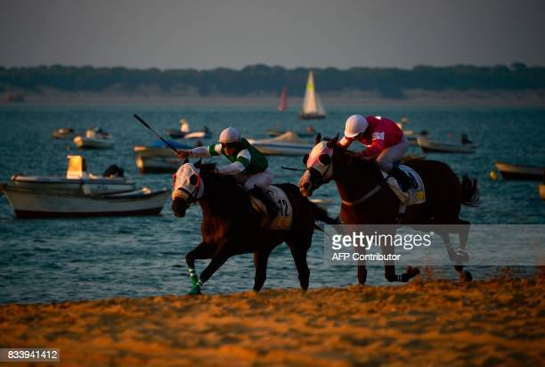 Jockeys race along the beach during the annual beach horse race at Sanlucar de Barrameda near Cadiz on August 17 2017 / AFP PHOTO / CRISTINA QUICLER