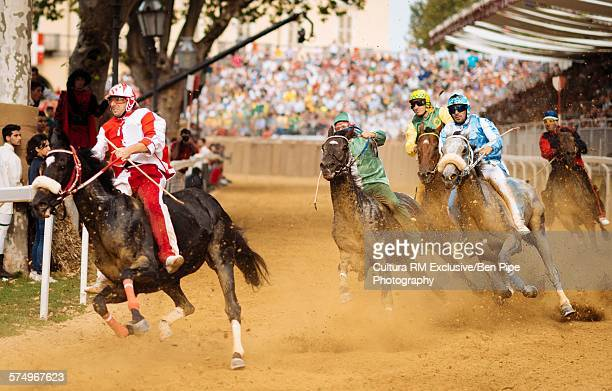 Jockeys racing bareback on horses at Palio di Asti medieval festival, Asti, Piedmont, Italy