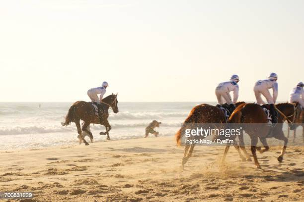 Jockeys Riding Horses On The Beach