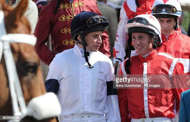 Jockeys Ryan Moore and Paul Hanagan chat as they enter the parade ring during Day Four of the 2014 Welcome To Yorkshire Ebor Festival at York...