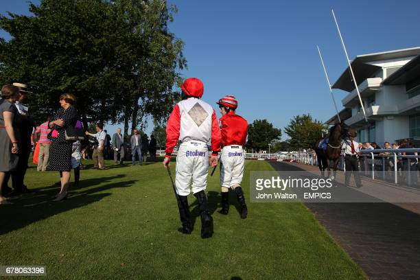 Jockeys trainers and owners in the parade ring at Epsom Downs prior to the Download Epsom's Android Or iPhone App Now Handicap
