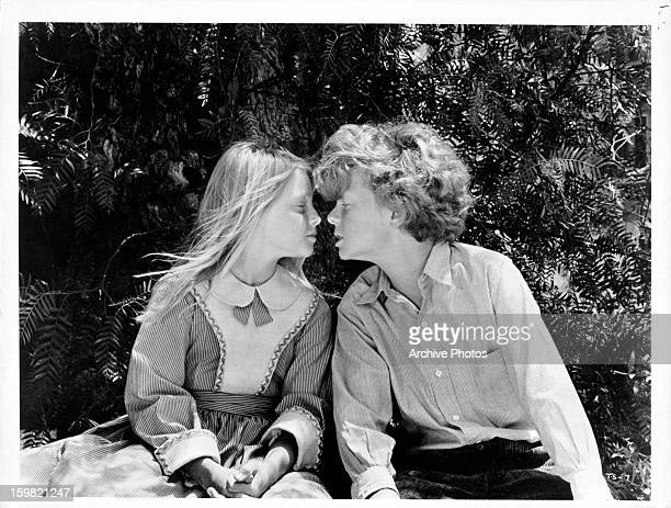 Jodie Foster and Johnny Whitaker about to kiss each other in a scene from the film 'Tom Sawyer' 1973