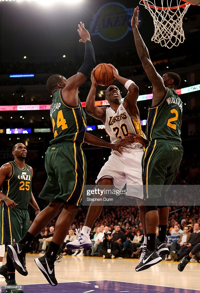 Jodie Meeks #20 of the Los Angeles Lakers goes up for a shot between Paul Millsap #25 and Marvin Williams #2 of the Utah Jazz at Staples Center on December 9, 2012 in Los Angeles, California. The Jazz won 117-110.