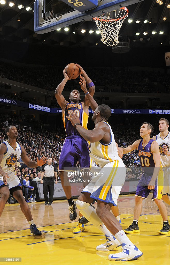 Jodie Meeks #20 of the Los Angeles Lakers goes up for the shot against Festus Ezeli #31 of the Golden State Warriors on December 22, 2012 at Oracle Arena in Oakland, California.