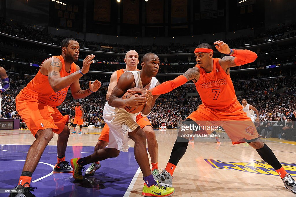 Jodie Meeks of the Los Angeles Lakers protects the ball against Carmelo Anthony of the New York Knicks at Staples Center on December 25 2012 in Los...
