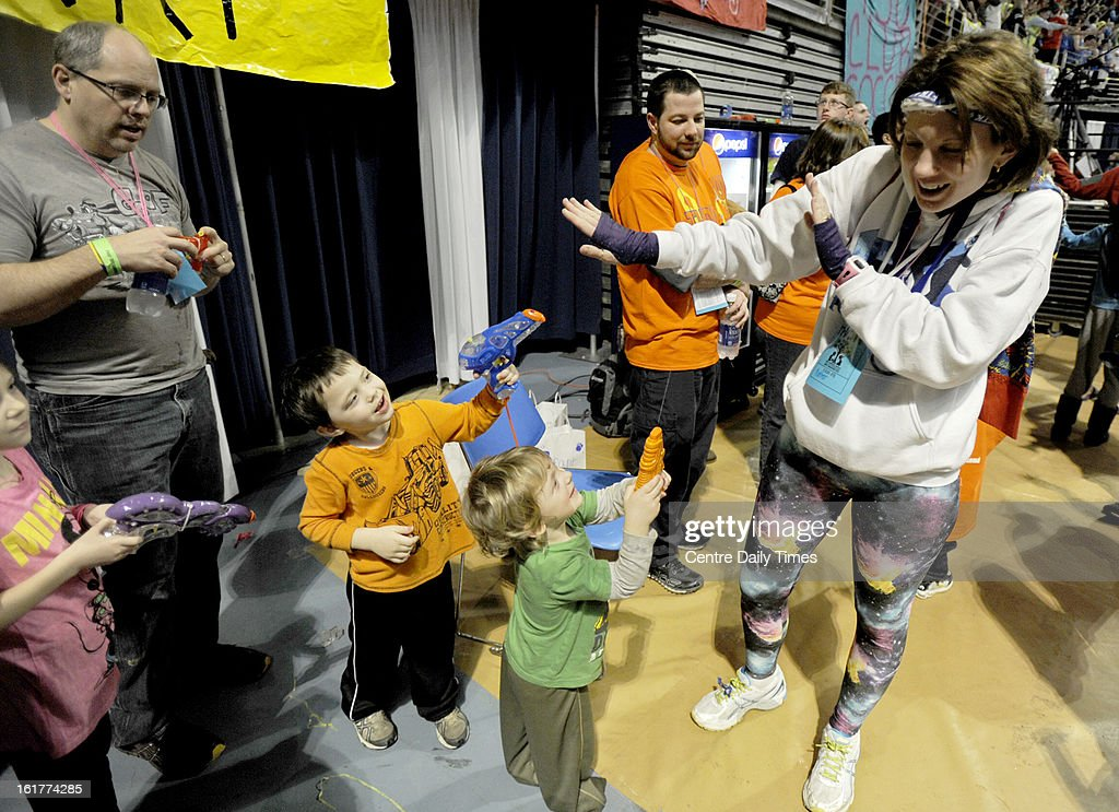 Jodie Potter is greeted by squirt guns from her children Manna, Jay, and Corban, after arriving at the Bryce Jordan Center for the Penn State IFC/Panhellenic Dance Marathon on Friday, February 15, 2013, in University Park, Pennsylvania. Potter came as part of was a group of 24 runners that completed a 135-mile journey from the pediatrics floor at Hershey Medical Center. The event raises money to help families that are battling pediatric cancer, including the Potters.