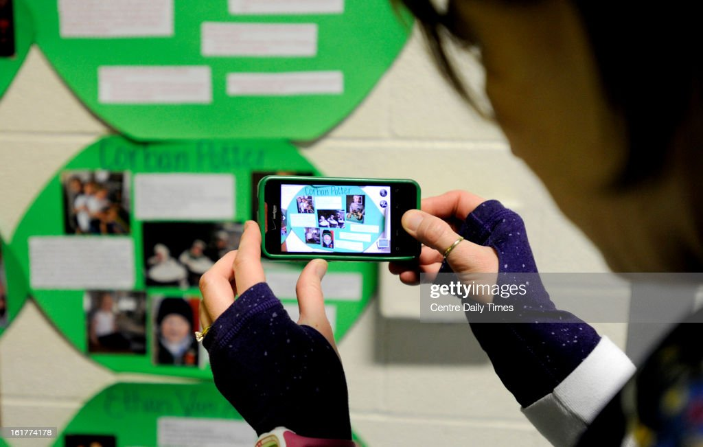 Jodie Potter takes a photo of a poster showing photos of her son, Corban, after arriving at the Bryce Jordan Center for the Penn State IFC/Panhellenic Dance Marathon on Friday, February 15, 2013, in University Park, Pennsylvania. Potter came as part of was a group of 24 runners that completed a 135-mile journey from the pediatrics floor at Hershey Medical Center. Corban has completed chemotherapy and is currently cancer free.