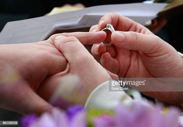Jodie VandermarkMartinez places a ring on the finger of her partner Jessica during a wedding ceremony on the steps of the Polk County Administration...