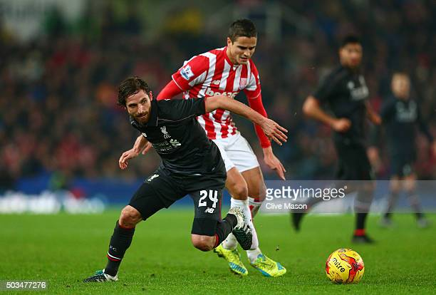 Joe Allen of Liverpool and Ibrahim Afellay of Stoke City compete for the ball during the Capital One Cup semi final first leg match between Stoke...