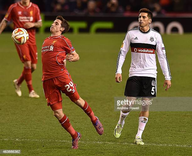 Joe Allen of Liverpool competes with Jose Sosa of Besiktas during the UEFA Europa League Round of 32 match between Liverpool FC and Besiktas JK on...
