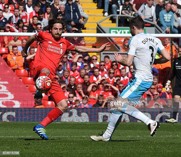 Joe Allen of Liverpool competes with Paul Dummett of Newcastle United during the Barclays Premier League match between Liverpool and Newcastle United...