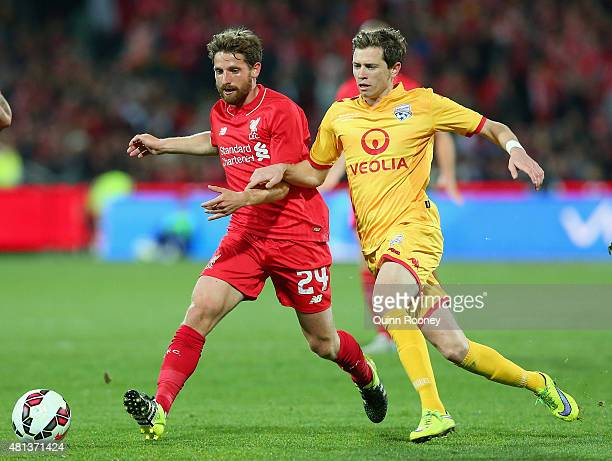 Joe Allen of Liverpool FC and Craig Goodwin of United compete for the ball during the international friendly match between Adelaide United and...