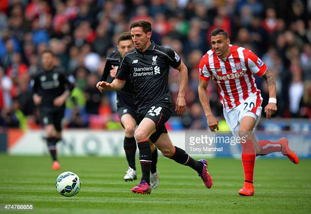 Joe Allen of Liverpool gets away from Geoff Cameron of Stkoe City during the Barclays Premier League match between Stoke City and Liverpool at...