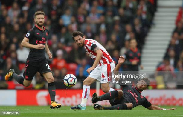 Joe Allen of Stoke City and Alex OxladeChamberlain of Arsenal battle for possession during the Premier League match between Stoke City and Arsenal at...