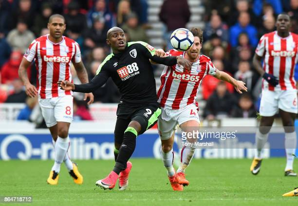 Joe Allen of Stoke City battles for the ball with Benik Afobe of AFC Bournemouth during the Premier League match between Stoke City and AFC...