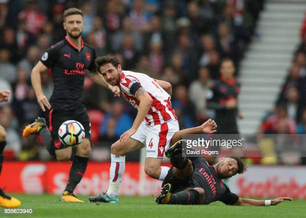 Joe Allen of Stoke City is challenged by Alex OxladeChamberlain during the Premier League match between Stoke City and Arsenal at Bet365 Stadium on...