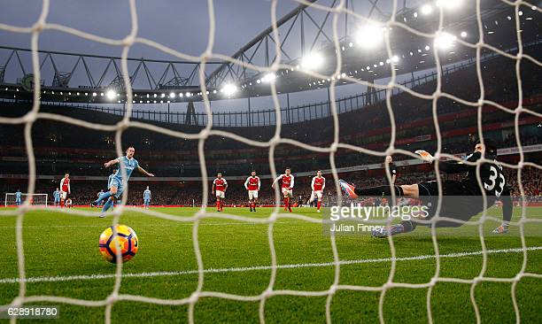 Joe Allen of Stoke City scores his sides first goal from the penalty spot beating Petr Cech of Arsenal during the Premier League match between...
