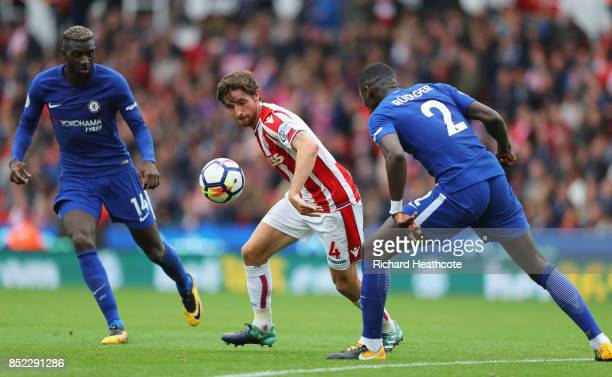Joe Allen of Stoke City taks on Antonio Rudiger of Chelsea during the Premier League match between Stoke City and Chelsea at Bet365 Stadium on...