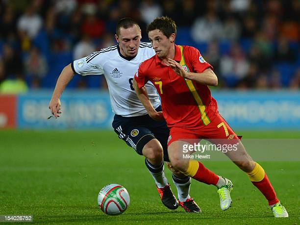Joe Allen of Wales gets past Scott Brown of Scotland during the FIFA 2014 World Cup Group A Qualifier between Wales and Scotland at City of Cardiff...