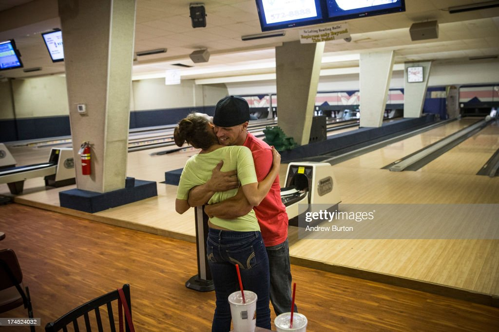 Joe Beach, originally from Fort Myers, FL, and Cici Borash, orginally from Saint Cloud, MN, embrace while bowling on July 26, 2013 in Williston, North Dakota. The two both came to North Dakota for work created by the oil boom, and met while working at an oil hauling company. North Dakota has been experiencing an oil boom recently, bringing tens of thousands of jobs to the region, lowering state unemployment and bringing a surplus to the state budget.