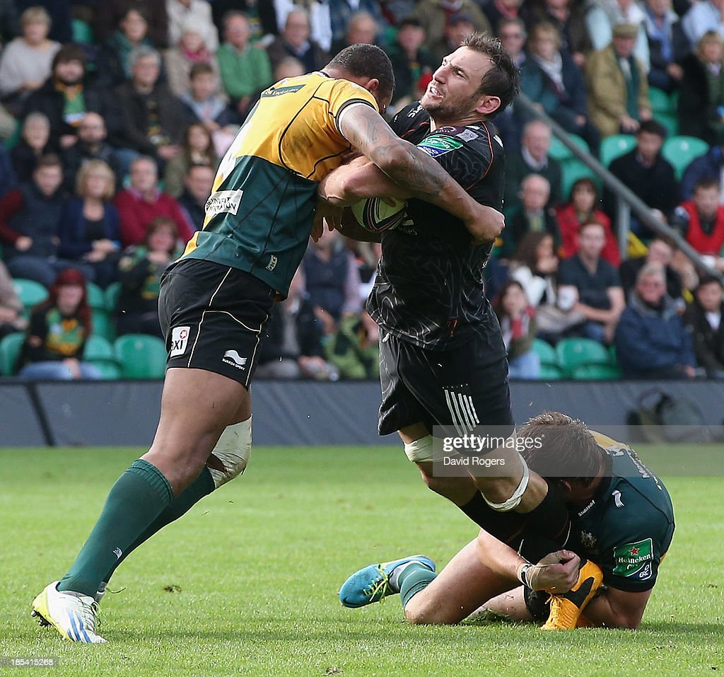 Joe Bearman of the Ospreys is tackled by Tom Wood and <a gi-track='captionPersonalityLinkClicked' href=/galleries/search?phrase=Courtney+Lawes&family=editorial&specificpeople=5385543 ng-click='$event.stopPropagation()'>Courtney Lawes</a> (L) during the Heineken Cup pool 1 match between Northampton Saints and Ospreys at Franklin's Gardens on October 20, 2013 in Northampton, England.