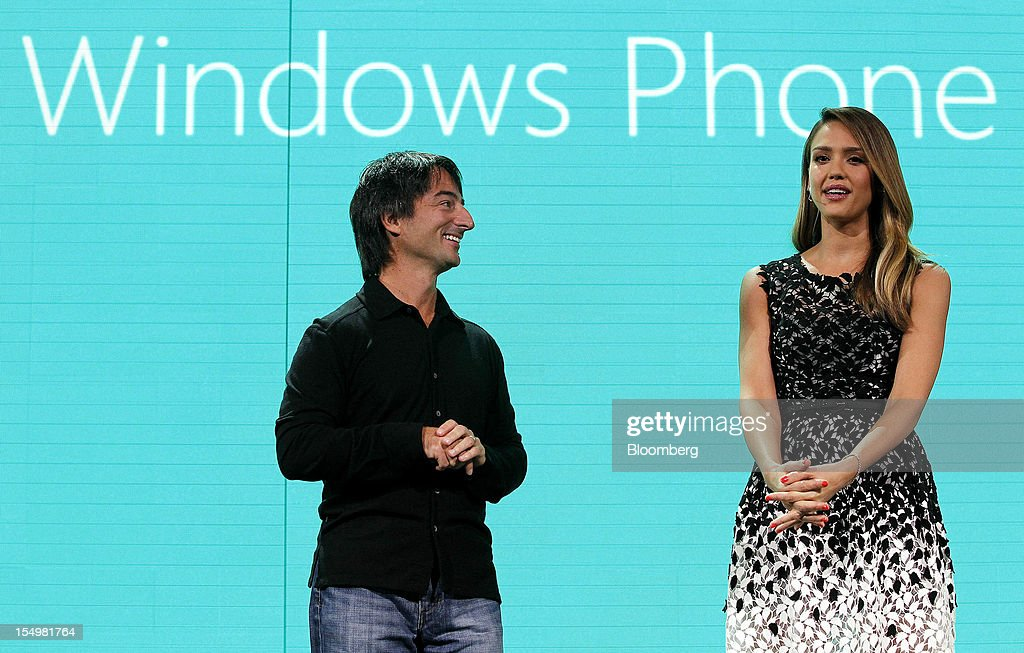 Joe Belfiore, vice president at Microsoft Corp., left, listens to actress <a gi-track='captionPersonalityLinkClicked' href=/galleries/search?phrase=Jessica+Alba&family=editorial&specificpeople=201811 ng-click='$event.stopPropagation()'>Jessica Alba</a> speak at an event to unveil Windows Phone 8 software in San Francisco, California, U.S., on Monday, Oct. 29, 2012. Microsoft Corp. unveiled a new version of its software for smartphones today, redoubling an effort to regain market share lost to Apple Inc. and Google Inc. Photographer: Tony Avelar/Bloomberg via Getty Images