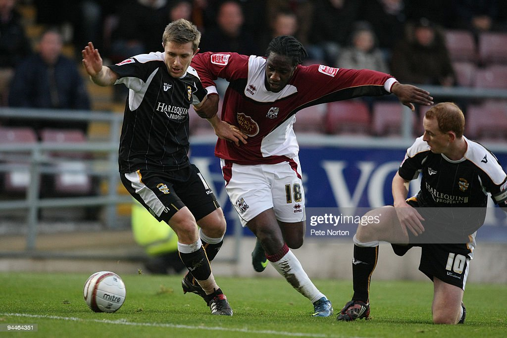 Joe Benjamin of Northampton Town contests the ball with Adam Yates of Port Vale as Tommy Fraser looks on during the Coca Cola League Two Match between Northampton Town and Port Vale at Sixfields Stadium on December 12, 2009 in Northampton, England.