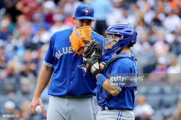 Joe Biagini of the Toronto Blue Jays and Raffy Lopez of the Toronto Blue Jays discuss play in the first inning against the New York Yankees at Yankee...