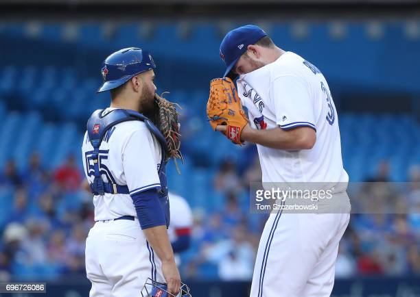 Joe Biagini of the Toronto Blue Jays is visited on the mound by Russell Martin in the first inning during MLB game action against the Chicago White...