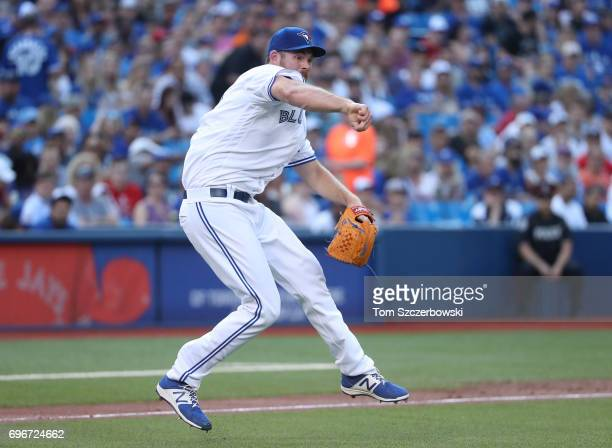 Joe Biagini of the Toronto Blue Jays makes a throwing error allowing a run to score in the first inning during MLB game action against the Chicago...