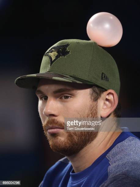 Joe Biagini of the Toronto Blue Jays sits in the dugout unaware that a bubble has been placed on top of his hat during MLB game action against the...